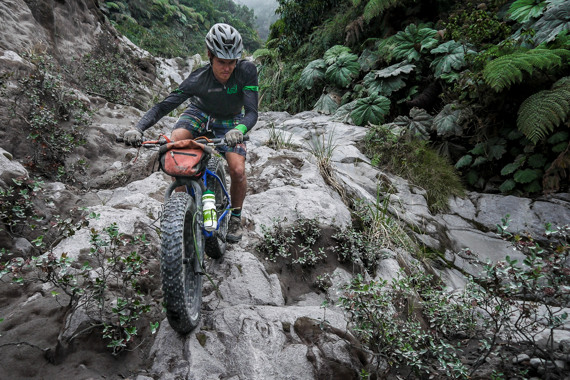 Brendan dodging holes and riding ridges on the slick, ash-covered dry lava flow en route to Volcán Santiaguito one of guatemala's hardest volcanos to reach.  Rider: Elizabeth Sampy Location: Volcán Santiaguito, Quetzaltenango, Guatemala