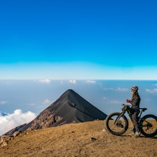 The dream achieved - Liz takes in the morning view of  Volcán Fuego from the summit of Volcán Acatenango. This image was featured on the cover of Mountain Flyer issue #49 | Volcán Acatenango (3,880m) , GuatemalaFilename: VC2016_EP03-ACAT-0329-G7-063-EditOriginal Date: 03/29/2016© 2016 Brendan James Photography www.picsporadic.com