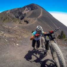 Liz Pushes the fatbike up Yepocapa, or Tres Hermanas - the secondary peak of Volcán Aacatenango. Behind you can see the deeply erroded hiking trail which we used to reach the summit the night before. | Volcán Acatenango (3,880m) , GuatemalaFilename: VC2016_EP03-ACAT-0329-GOPRO-41Original Date: 03/29/2016© 2016 Brendan James Photography www.picsporadic.com